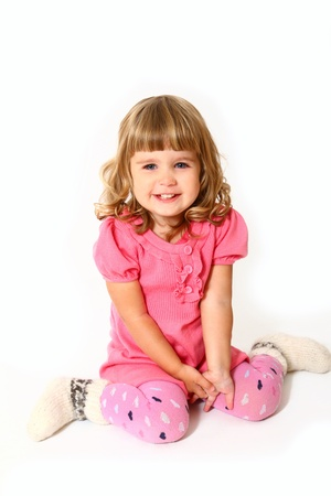 Happy little girl in a pink dress sitting Stock Photo - 16669104