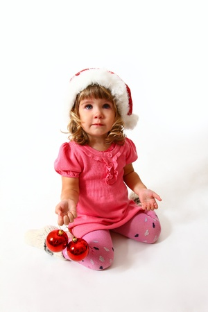 Christmas sweet baby sitting with Santa Claus hat and red balls photo