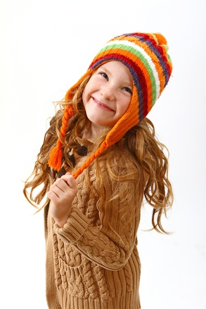 sweater girl: Happy little girl in colorful cozy sweater and hat