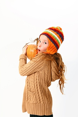 pumpkin face: Portrait of surprised little girl with pumpkins and colored clothing