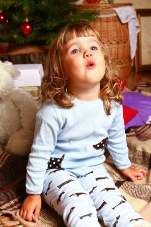 Little girl sits on a brown plaid near New Year or Christmas tree photo