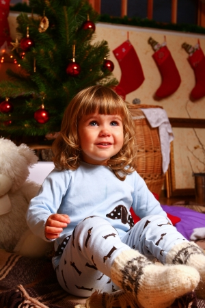 Smiling baby sitting on a plaid near a Christmas tree photo