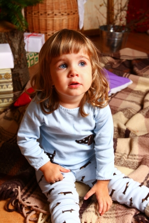 Baby in pajamas sitting on a plaid near a Christmas tree photo