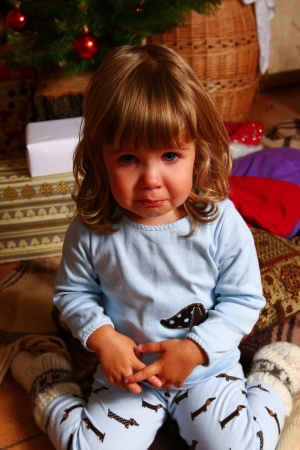 Crying baby sitting on a plaid near a Christmas tree photo
