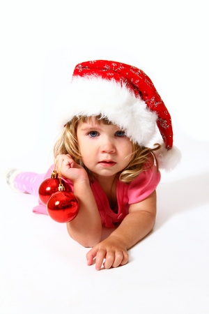 Pretty baby with Santa Claus hat lying  and holding  red balls photo