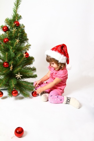 Little girl sitting near New Year or Christmas tree and holding a red ball photo