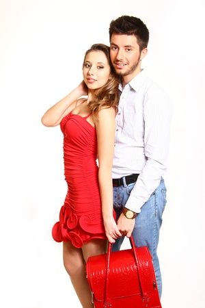 Romantic young couple holding a red bag