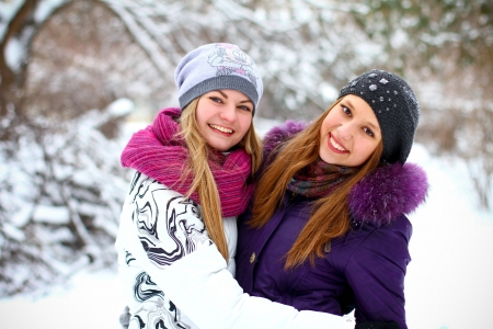 Two happy young girls having fun in winter park photo