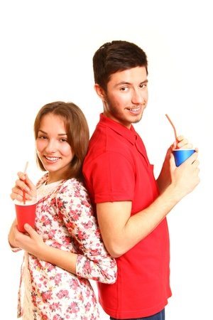 Happy young couple standing back to back and drinking from cups  photo