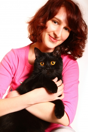 Beautiful young woman holding a black British cat photo