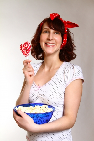 Smiling young woman with popcorn and lollipopg photo