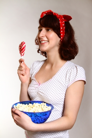 Portrait of happy girl with lollipop and popcorn watching photo