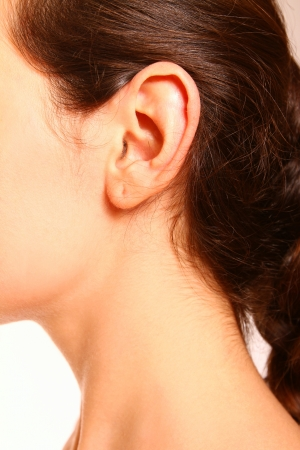 A close-up portrait of a female ear and neck on white background