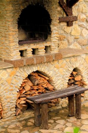 Rokerige antieke bakstenen oven buiten met brandhout en een bankje buiten