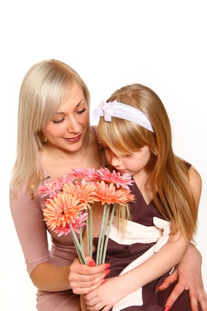 olfaction: Happy mother and daughter sniffing flowers and hugging Stock Photo