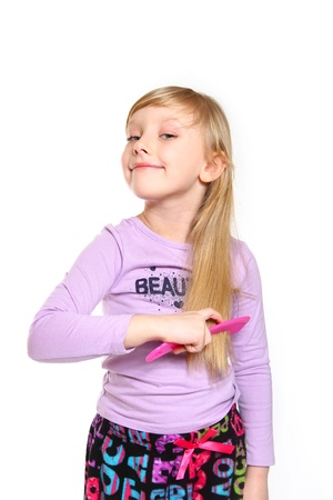 Blonde little girl combing her hair Stock Photo - 18008949