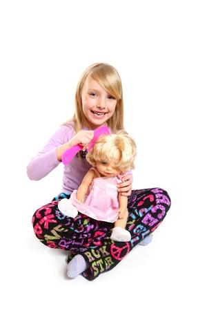 Glimlachend meisje kammen haar pop het haar geïsoleerd op witte achtergrond