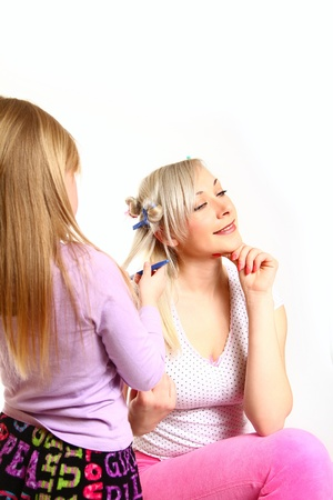 Daughter styling her mother's hair  isolated on white background Stock Photo - 18034561