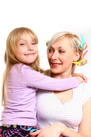 Smiling daughter hugging her mother with curlers photo