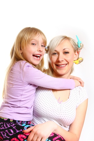Happy mother and daughter with hair curlers hugging photo