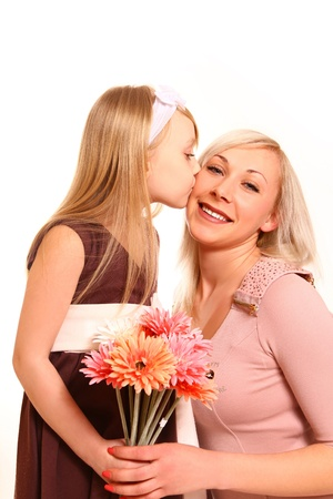 Little girl with flowers kisses her mother photo