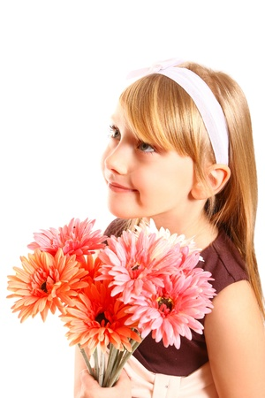 Smiling little girl with gerberas on a white background closeup photo