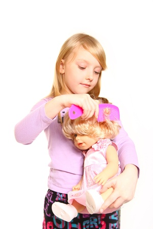 Little girl combing hair her doll on white background photo