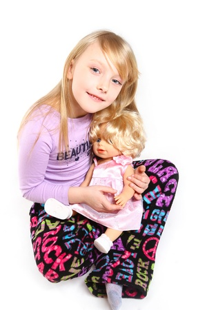 Cute little girl with doll sitting on white background photo