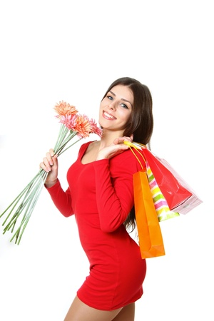 Beautiful girl with shopping bags and a bouquet of gerberas