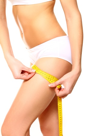 Woman measuring her thigh with a yellow metric tape measure on white background