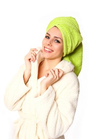 Glimlachende jonge vrouw in een gewaad met handdoek op haar hoofd