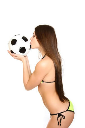 Girl in a swimsuit holding and kissing a soccer ball on white background photo
