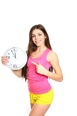 Attractive athletic girl with a clock on a white background photo