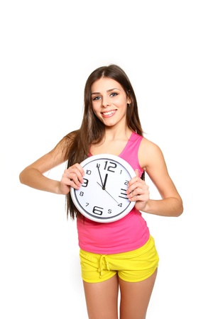 Attractive athletic girl with a clock on white background  Time for sport photo
