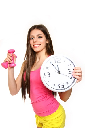 Attractive young woman with a clock and dumbbells on white background