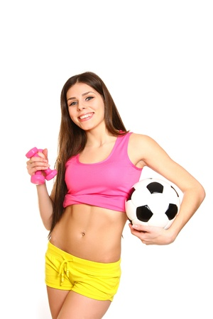 Cute fitness girl posing with dumbbells and a soccer ball on  white background photo