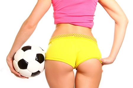 Athletic woman posing with a soccer ball on  white background, rear view