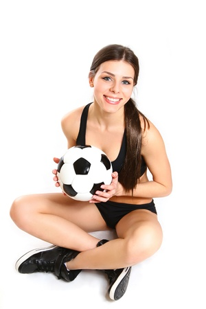 Sexy girl is sitting with a soccer ball on white background from above photo