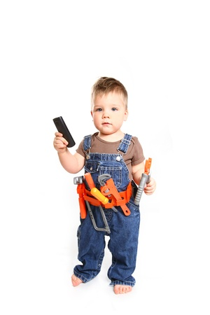 Little boy  with tools and mobile phone on a white background photo