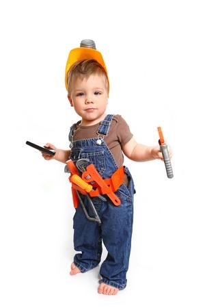 Kleine jongen in een oranje helm met gereedschap en een mobiele telefoon op witte achtergrond Stockfoto