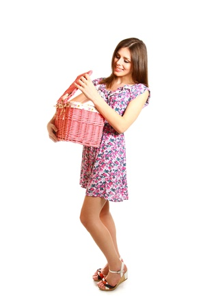household tasks: Cute young woman with a laundry basket on a white background