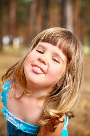 Cheerful little girl shows tongue in  forest photo