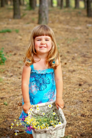 Happy little girl standing with a basket of flowers in  forest photo