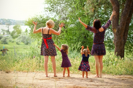 Two mothers with their daughters on field in summer photo
