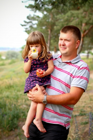Little girl with dad in  forest, girl drinking milk and eating bread photo