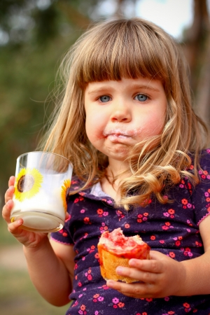 Little girl eating bread and drinks milk, outdoors photo