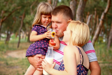 Picnic in the woods,  daughter  giving to drink of her father photo