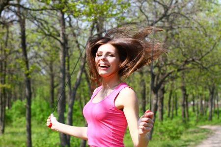 Happy young woman jumping with a skipping rope in  summer park