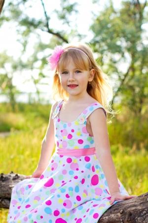 Portrait of  little girl sitting on  tree branch photo