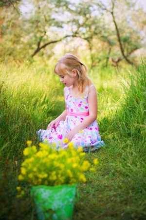 Portrait of little girl with a bucket of flowers in  summer garden photo